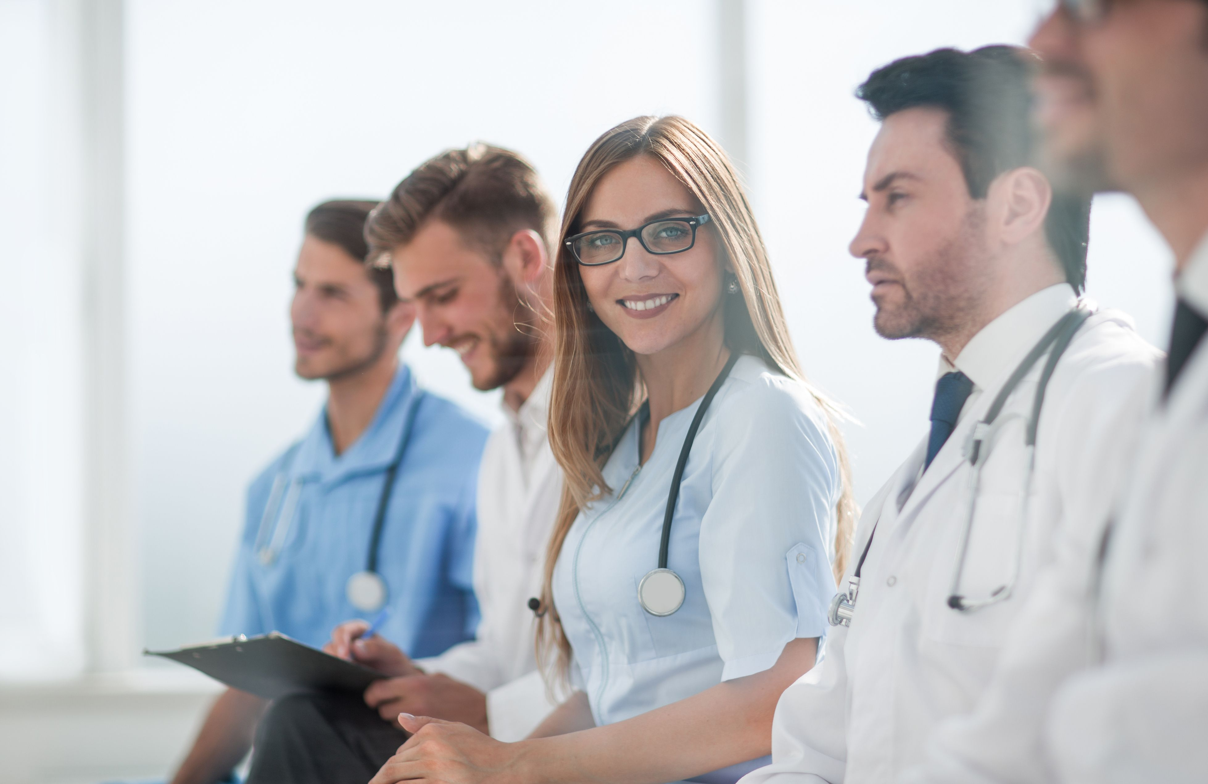 Portrait of female doctor with colleagues at meeting